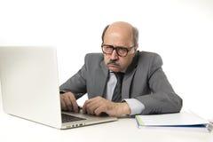 Älterer reifer beschäftigter Geschäftsmann mit Kahlkopf auf seiner Funktion 60s betont und frustriert am Bürocomputer-Laptopschre lizenzfreie stockfotografie