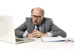 Älterer reifer beschäftigter Geschäftsmann mit Kahlkopf auf seiner Funktion 60s betont und frustriert am Bürocomputer-Laptopschre stockfotografie