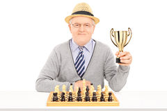 Älterer Schachspieler, der eine Trophäe hält Stockfotografie