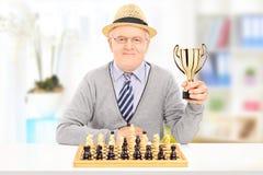 Älterer Schachspieler, der zuhause eine Trophäe hält Stockfoto