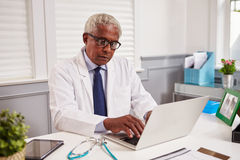 Älterer schwarzer männlicher Doktor im weißen Mantel, der in einem Büro arbeitet lizenzfreie stockbilder