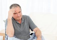 Älterer in seinem Rollstuhl, der Kopfschmerzen hat lizenzfreie stockbilder