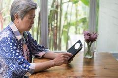 Älterer Senior, der soziales und Lebensstilnachrichten mit APP in MO überprüft Lizenzfreie Stockfotos