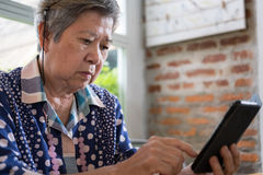 Älterer Senior, der soziales und Lebensstilnachrichten mit APP in MO überprüft Stockfotos