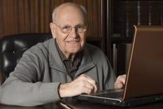 Älterer stattlicher Mann auf Laptop stockfoto