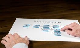Älterer Technologe, der auf blockchain Illustration zeigt Lizenzfreies Stockfoto