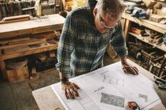Älterer Tischler, der Plan an der Werkstatt studiert lizenzfreie stockfotografie