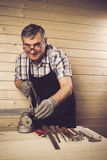 Älterer Tischler, der in seiner Werkstatt arbeitet Stockbilder