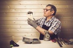 Älterer Tischler, der in seiner Werkstatt arbeitet Lizenzfreie Stockfotografie