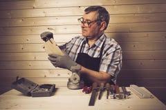 Älterer Tischler, der in seiner Werkstatt arbeitet Lizenzfreies Stockbild