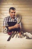 Älterer Tischler, der in seiner Werkstatt arbeitet Lizenzfreies Stockfoto