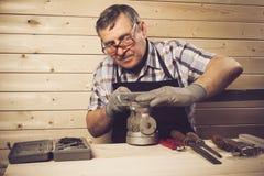 Älterer Tischler, der in seiner Werkstatt arbeitet lizenzfreie stockfotos