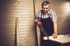 Älterer Tischler, der in seiner Werkstatt arbeitet stockfoto