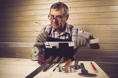 Älterer Tischler, der in seiner Werkstatt arbeitet Stockfotografie