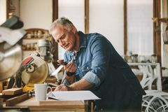 Älterer Tischler, der an seiner Werkstatt arbeitet stockfotografie