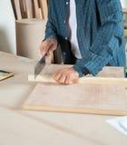 Älterer Tischler kleines Cutting Wood With sah Lizenzfreies Stockfoto