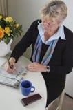 Älterer tut ein Kreuzworträtsel im newspape Lizenzfreies Stockfoto