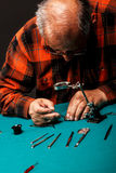 Älterer Uhrmacher, der eine alte Taschenuhr repariert Stockfoto