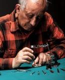 Älterer Uhrmacher, der eine alte Taschenuhr repariert Lizenzfreie Stockbilder