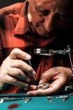 Älterer Uhrmacher, der eine alte Taschenuhr repariert Lizenzfreie Stockfotos