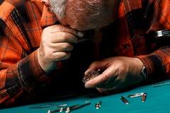 Älterer Uhrmacher, der eine alte Taschenuhr repariert Stockbild