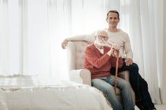 Älterer unshaken Mann, der auf dem Stuhl sitzt und gerade schaut stockbild