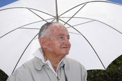 Älterer unter einem Regenschirm Stockbild