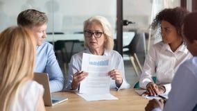 Älterer Unternehmensleiter, der Finanzberichtsergebnis bei der Teambesprechung darstellt stockfoto