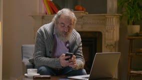 Älterer Unternehmer, der mit dem Smartphone und Laptop-Computer festlegen Business-Lunch-Zusammenkunft arbeitet stock footage