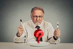 Älterer verblüffter Mann, der Mahlzeit wählt stockbilder