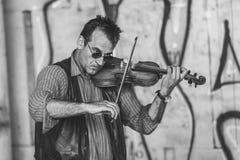 Älterer Violinist, der auf einer Straße spielt Stockfotografie