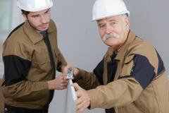 Älterer Vorarbeiter mit jüngerer Arbeitskraft Stockbilder