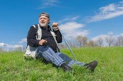 Älterer Wanderer, der auf grünem Hügel sitzt Lizenzfreies Stockbild