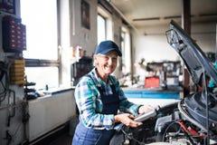 Älterer weiblicher Mechaniker, der ein Auto in einer Garage repariert Lizenzfreie Stockfotografie