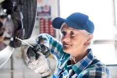 Älterer weiblicher Mechaniker, der ein Auto in einer Garage repariert Stockbild