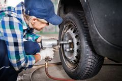 Älterer weiblicher Mechaniker, der ein Auto in einer Garage repariert Stockfotografie