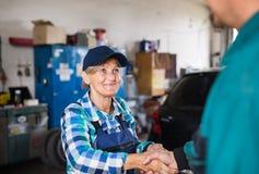 Älterer weiblicher Mechaniker, der ein Auto in einer Garage repariert Stockfotos