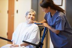 Älterer weiblicher Patient, der Rollstuhl von der Krankenschwester eingedrückt wird stockbild