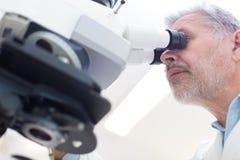 Älterer Wissenschaftler, der im Labor microscoping ist Stockfoto