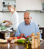 Älteres älteres vorbereitendes vegetarisches Lebensmittel und reifes Frauhandeln Stockfotografie