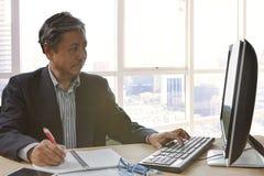 Älteres asain Geschäftsmannschreiben und -funktion auf PC computor Stockbild