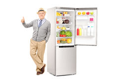 Älteres auf einem Kühlschrank sich lehnen und Daumen aufgeben Stockfotografie