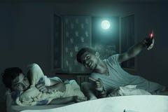Älteres Bruderlachen hinunter den erschrockenen und schlaflosen Jungen Stockfotos