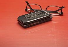 Älteres Celluar-Telefon und schwarze Rahmen-Gläser Stockfotos