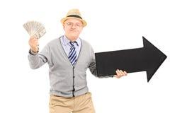 Älteres erwachsenes haltenes Geld und ein großer schwarzer Pfeil Lizenzfreie Stockfotos