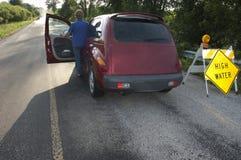 Älteres Frauen-Laufwerk-gefährliche Straßenzustand-Flut Stockfoto