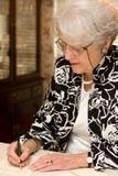 Älteres Frauen-Schreibens-Zeichen Lizenzfreies Stockfoto