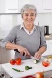 Älteres Frauenausschnittgemüse in der Küche lizenzfreies stockfoto