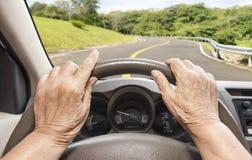 Älteres Frauenautofahren auf Landstraße lizenzfreie stockfotografie