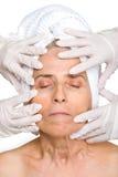 Älteres Frauengesicht in den Gummihandschuhhänden Lizenzfreie Stockfotos